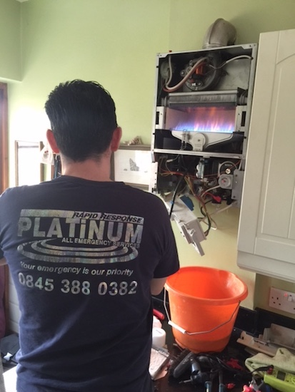 Emergency plumbing and heating engineer standing in front of a boiler carrying out fault finding test.