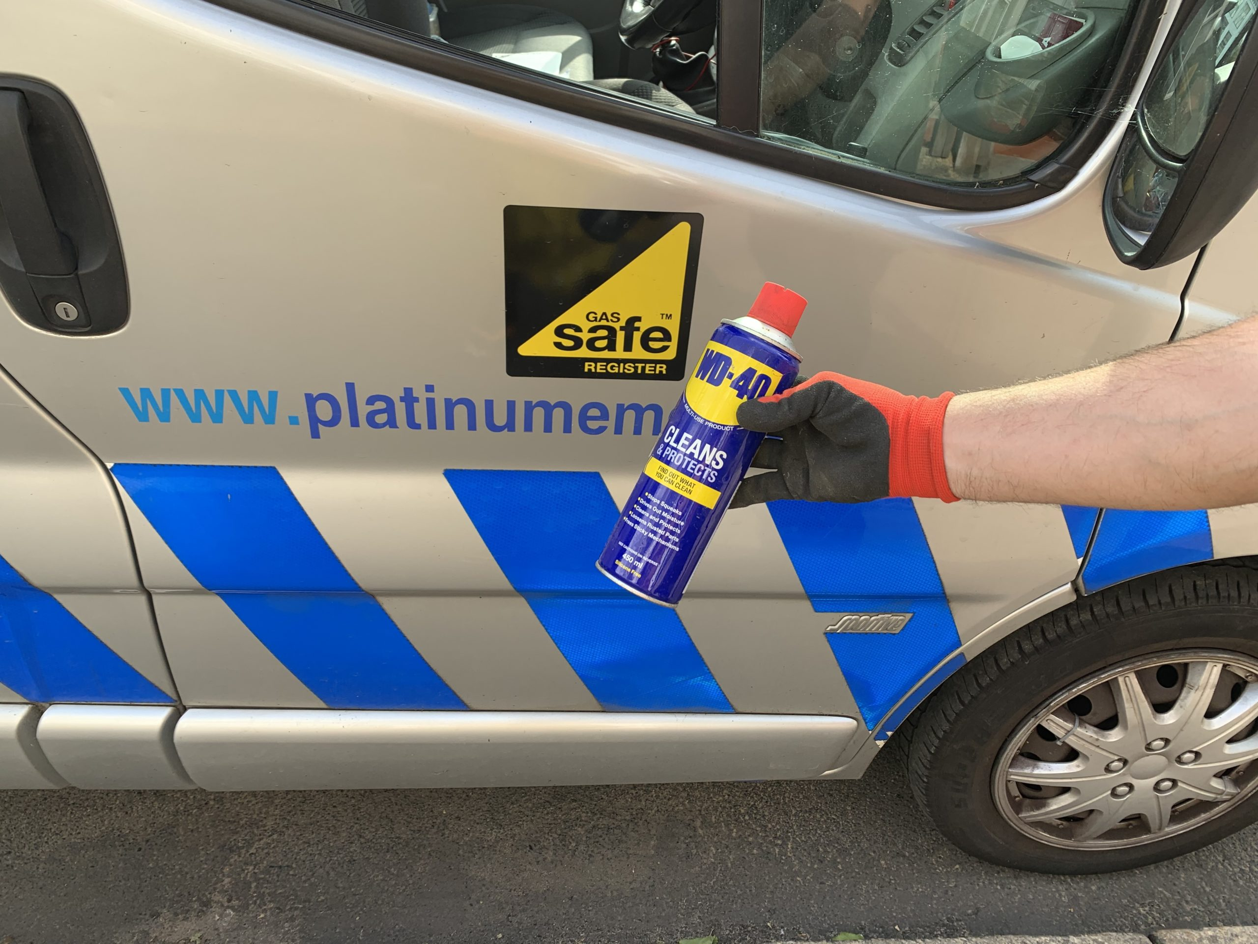 Photo with person holding can of WD40. In the background is website www.platinumemergency.com