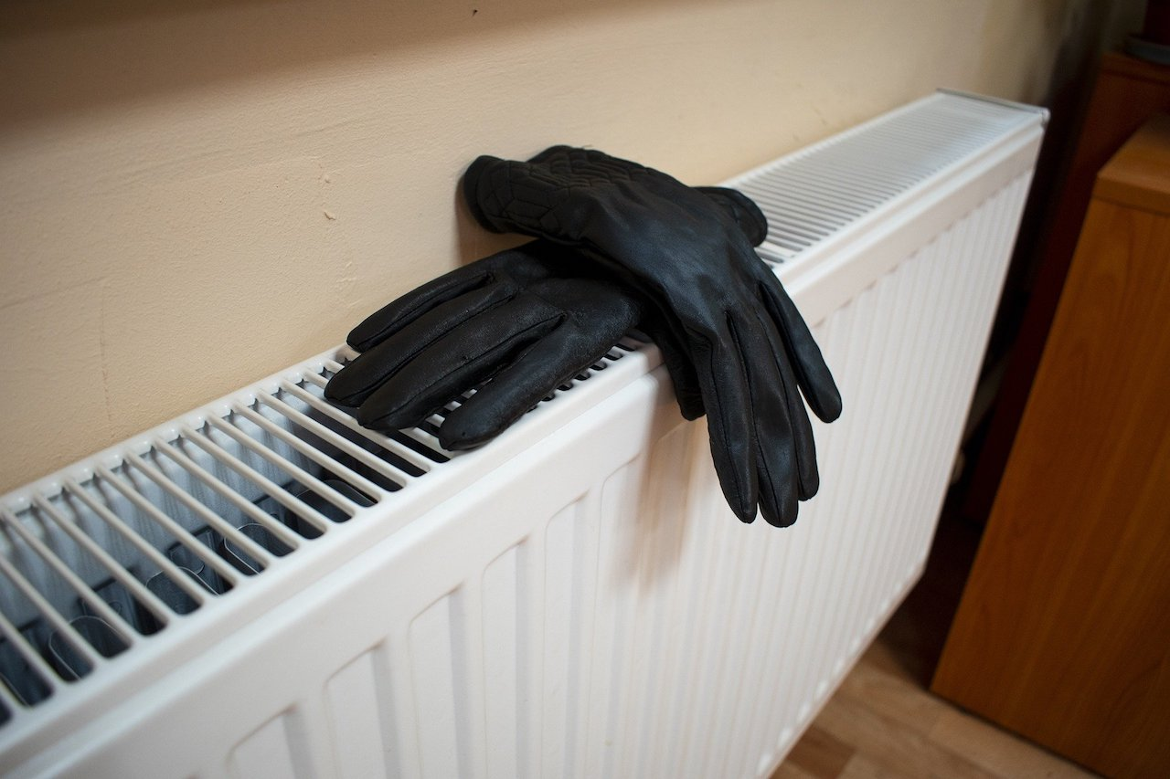 Photo showing a single panel radiator with a pair of black gloves on it.